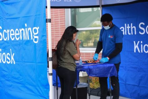 A woman takes a COVID-19 nasal swab test in front of a World Back to Work Staff member at El Camino College on Monday, Aug. 30. All students and employees who are unvaccinated must take a COVID-19 test before entering campus grounds. Mari Inagaki/ The Union.