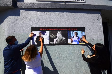 """Members and friends of the Hernandez family prepare to tape a printed poster with three images of Juan Carlos Hernandez over the wall outside the dispensary where he worked and was allegedly murdered by suspects Ethan Kedar Astaphan, Sonita Heng and Weijia Peng on Sept. 22, 2020. The case is ongoing. Astaphan and Hang were eventually captured and arrested last November. Peng is currently in custody in Turkey where he is attempting to fight his extradition to the United States. """"All year I wanted to go back to the last place [Juan] took his last breath,"""" Juan Hernandez&squot;s mother, Yajaira Hernandez, said. """"That place was where we wanted to do a small vigil and pray for Juan&squot;s soul."""""""