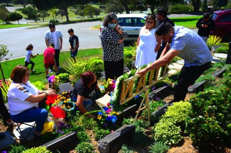 Family and friends gather around Juan Carlos Hernandez's grave where Jose Guadalupe Hernandez, far right, attaches a floral bouquet with his son's name to the tombstone where some of his ashes are buried at the Holy Cross Catholic Cemetery in Culver City. Photo by Jose Tobar/The Union
