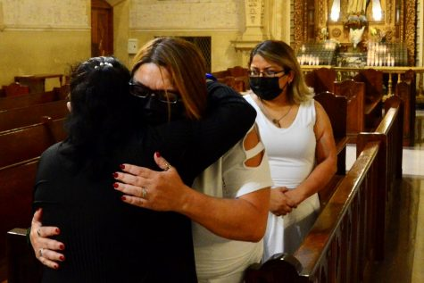 Juan Carlos Hernandez's mother, Yajaira Hernandez, receives a hug from a woman at the conclusion of the mass memorial at the Saint Paul de Vincent Parish in Los Angeles. Her sister Stephanie Pineda, far right, stands back with hands clasped. Photo by Jose Tobar/The Union