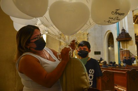 """Juan Carlos Hernandez&squot;s aunt, Stephanie Pineda, left, prepares a set of balloons that read """"Forever in Our Hearts"""" while her son, Nathan Melendez, 11, looks on during the Memorial Mass in Hernandez&squot;s honor on Wednesday, Sept. 22, 2021."""