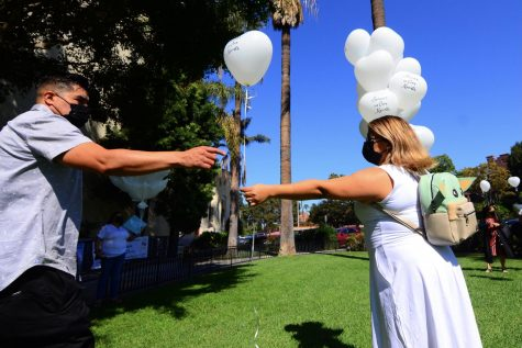 """Juan Carlos Hernandez&squot;s father, Jose Hernandez, takes a balloon from Stephanie Pineda on the lawn of the Saint Vincent de Paul Parish in Los Angeles. The balloons with the inscription """"Forever in Our Hearts"""" will be released"""