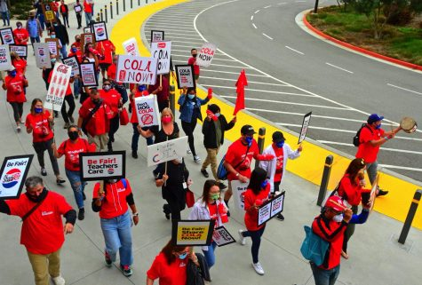 """A large crowd of El Camino College Teachers' Federation members and their supporters march past the Student Services building during their educational campaign on Thursday, October 7, 2021, chanting, """"What do we want?  COLA.  When do we want it?  Now."""